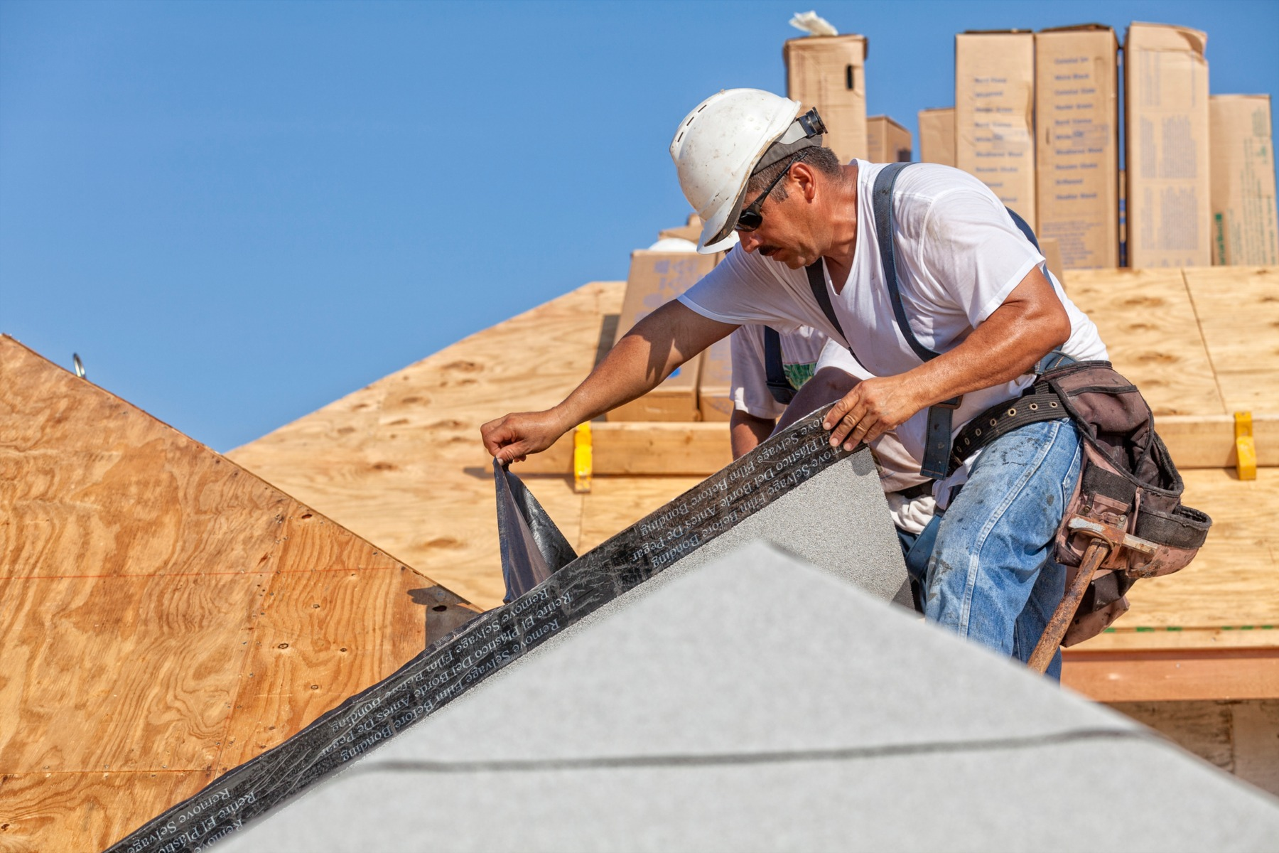 Roofer tears off protective cover of underlayment on a new roo