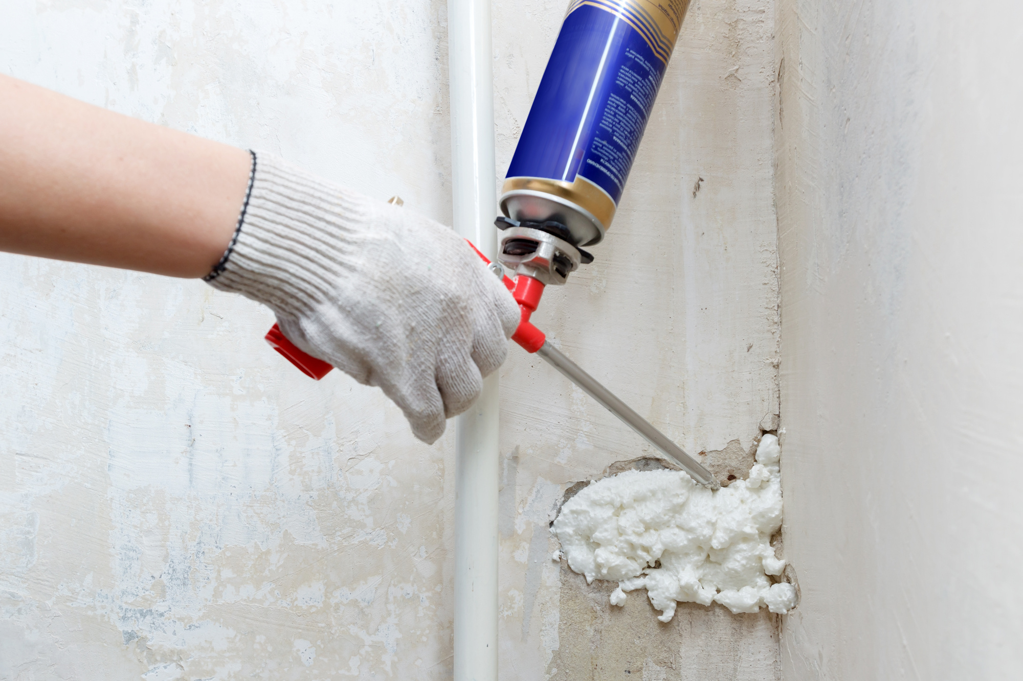 Worker's hand fix a rent in wall using polyurethane foam