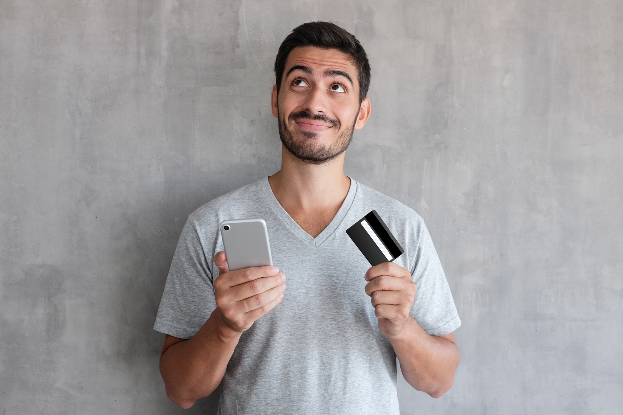 Young handsome man thinking about online shopping via internet, wearing gray t shirt, standing against textured wall, holding credit card and cell phone
